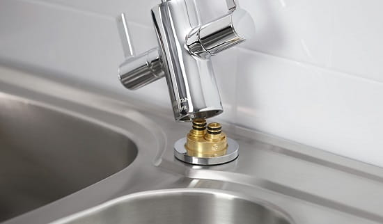 An image of an easy fit bristan kitchen tap being installed onto a kitchen sink